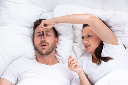 Frustrated Young Woman Trying To Stop Man's Snoring With Clothespin On Bed
