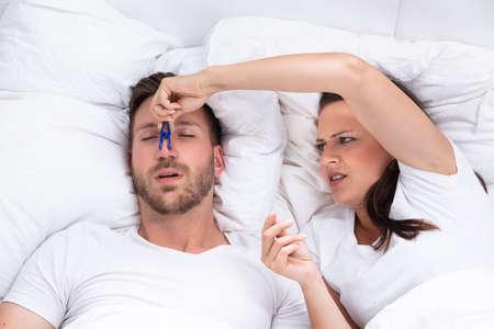 Gefrustreerde Jonge Vrouw Die Man's Snurken Met Wasknijper Op Bed Probeert Te Stoppen