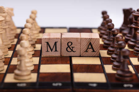 Échiquier avec des blocs en bois montrant le concept de fusions et d'acquisitions Banque d'images