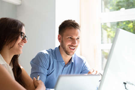 Two Happy Young Businesspeople Looking At Computer In Office Stock Photo