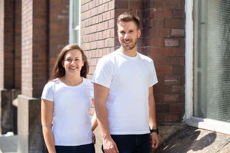 Portrait Of A Smiling Young Couple Standing On Street