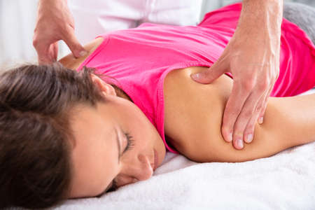 Close-up Of A Therapists Hand Giving Shoulder Massage To Relaxed Female Patient