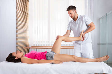 Male Therapists Hand Stretching Female Patients Leg In Clinic