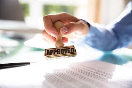 Nahaufnahme der Handstempelung einer Geschäftsfrau auf genehmigtem Vertragsformular Standard-Bild