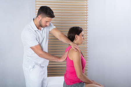 Thérapeute masculin massant le dos de la femme en clinique