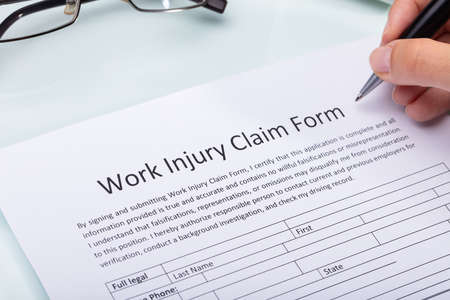 Close-up Of A Woman's Hand Filling Work Injury Claim Form 스톡 콘텐츠