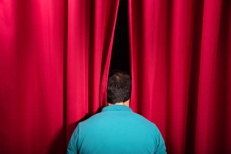 Rear View Of A Man Peeking Through A Red Stage Curtain