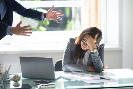ビジネスマンは、オフィスに座ってストレスの女性従業員を叱ります