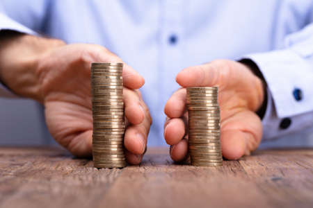 Nahaufnahme der Hand einer Person, die Stapel von Münzen hält