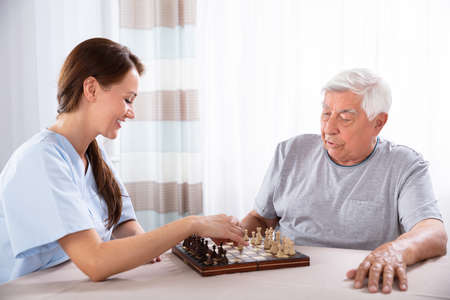 Young Female Caretaker Playing Chess With Senior Man At Home