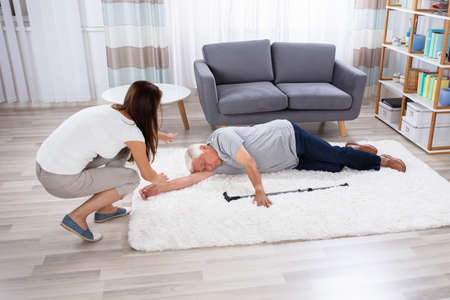Woman Looking At Her Unconscious Father Lying On Carpet Stock Photo