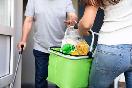 Senior Man With Walking Stick Offering Help To His Young Daughter Carrying Groceries Stock Photo