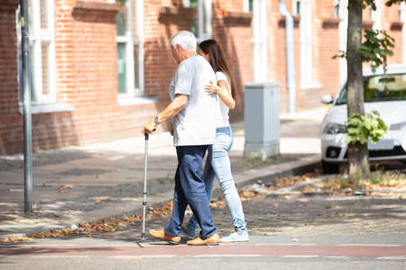 Side View Of A Young Woman Assisting Her Father While Crossing Road Stock Photo