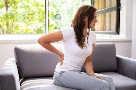 Woman Sitting On Sofa Suffering From Back Pain