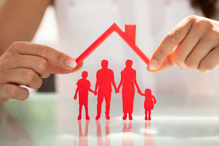 Businesswomans Hand Protecting Red Family Figures With Roof Over Reflective Desk Stock Photo