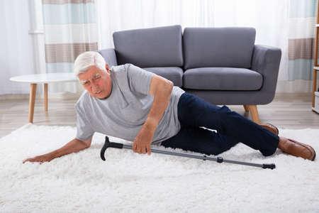 Senior Man Fallen On Carpet With Walking Stick