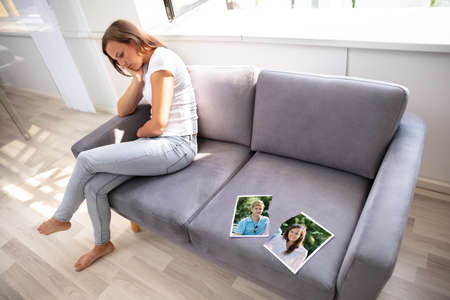 Lonely Woman Sitting On Sofa With Torn Photograph Stock Photo