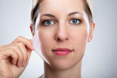 Porträt einer schönen jungen Frau, die schälende Maske von ihrem Gesicht entfernt