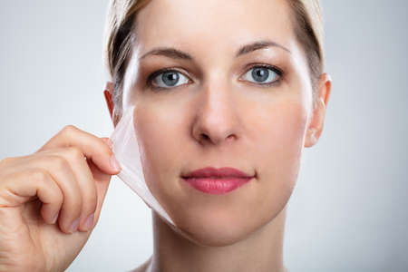 Portrait Of A Beautiful Young Woman Removing Peeling Mask From Her Face