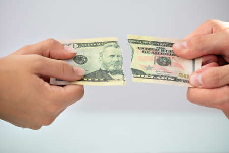 Close-up Of Two Businesspeople Hands Holding Torn American Banknote