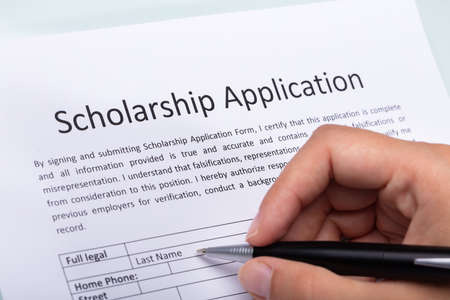 Close-up Of A Persons Hand Filling Scholarship Form With Pen Stock Photo