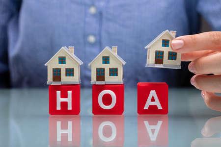 Zakenvrouw Hand Plaatsen Huismodellen Op Rode HOA Kubieke Blokken Over Bureau Stockfoto - 108864774