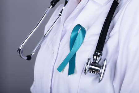 Médico con cinta verde azulado que apoya la concienciación sobre el cáncer de ovario