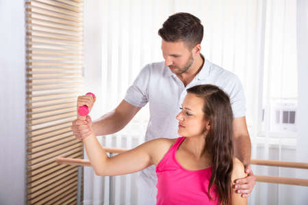 Male Therapist Assisting Young Female Patient While Exercising With Dumbbell Stockfoto