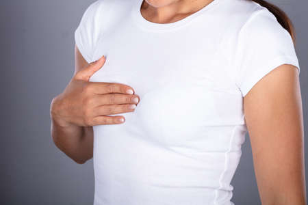 Womans Hand On Breast Suffering From Pain Stock Photo
