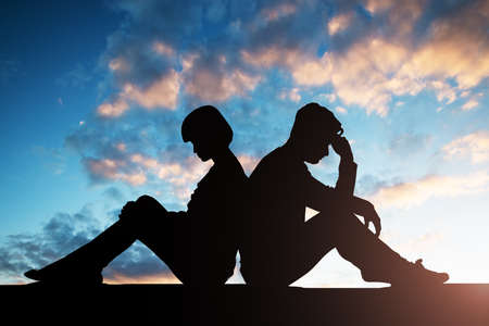 Silhouette Of Sad Couple Sitting Back To Back Against Cloudy Sky