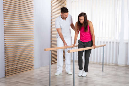 Therapists Assisting Female Patient In Walking With The Support Of Handrails Stock Photo