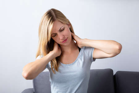 Young Woman Suffering From Neck Pain At Home