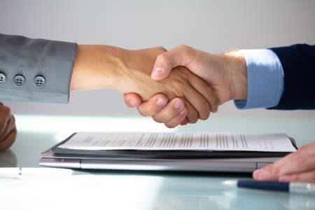 Business Partners Shaking Hands Over Contract Form