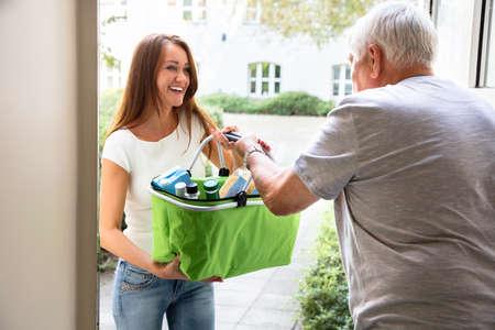 Senior Man with Walking Stick offrant de l'aide à sa jeune fille transportant des produits d'épicerie