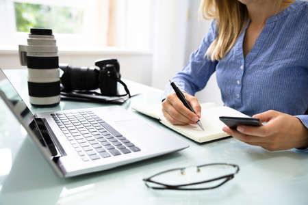 Female Editor Writing Notes In Diary With Laptop And DSLR Camera On Desk