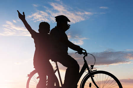Silhouette Of A Couple Enjoying Bicycle Ride At Sunset Фото со стока