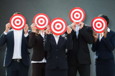 Group Of Businesspeople Hiding Their Faces Behind Dartboard On Grey Background Фото со стока