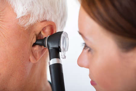 Close-up Of A Female Doctor Examining Senior Male Patients Ear With Otoscope