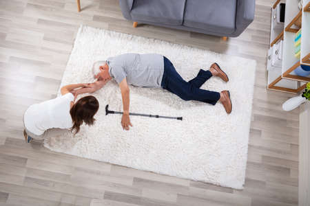 Woman Looking At Her Unconscious Father Lying On Carpet Foto de archivo