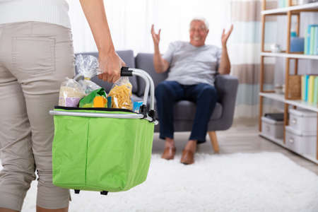 Father Looking At His Daughter Holding Groceries In Basket