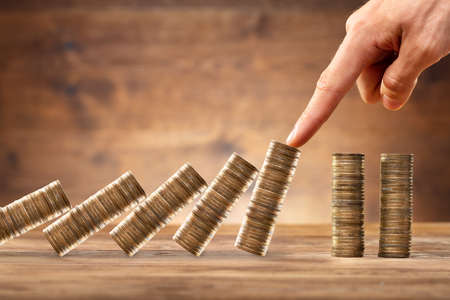 Close-up Of A Businesspersons Hand Protecting Stacked Coins From Falling On Wooden Desk
