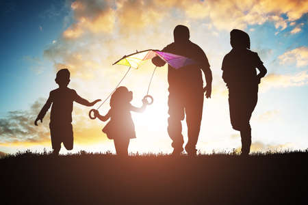 Silhouette Of Family Having Fun While Flying Colorful Kite During Sunset