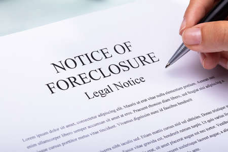 Close-up Of A Woman's Hand Holding Pen Over Notice Of Foreclosure Document