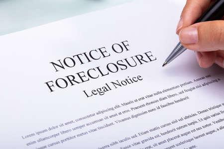 Close-up of a woman's hand holding pen sur avis de forclusion document Banque d'images