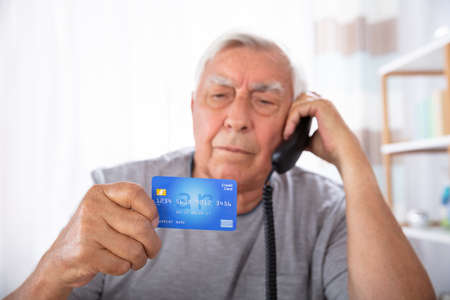 Close-up Of A Senior Man With Credit Card Using Landline Phone