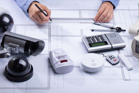 Architect Drawing Blueprint With Various Security Equipment On Desk