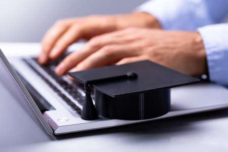 Businessperson Using Laptop With Black Graduation Hat On Keypad
