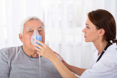 Young Female Doctor Holding Oxygen Mask Over Senior Male Patient's Face Stock Photo