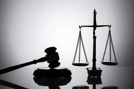 Silhouette Of Gavel And Justice Scale On Reflective Background