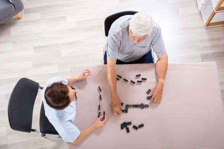 Elevated View Of Female Caretaker And Senior Man Playing Dominoes Фото со стока